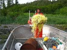 A man dressed in all orange stands in a boat holding a pile of yellow rope.