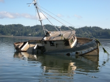 Ab abandoned vessel partly submerged in water.