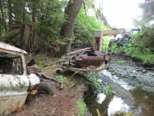 An abandoned vehicle is removed from a stream with heavy machinery.