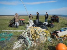 Volunteers around a pile of net and rope debris.