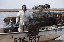 A man stands on a boat near derelict crab traps.