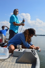 Three scientists collect water data from a boat.