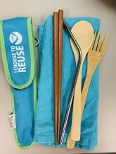 Bamboo silverware, chopsticks, and stainless steel straw rest on top of a cloth napkin.