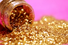 Gold glitter spills from a bottle onto a pink background.