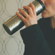 A person sipping from a reusable coffee mug.