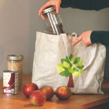Someone pulling a glass jar of food from a reusable bag with groceries on the counter.