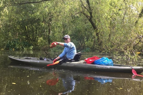 A volunteer in a kayak with debris.