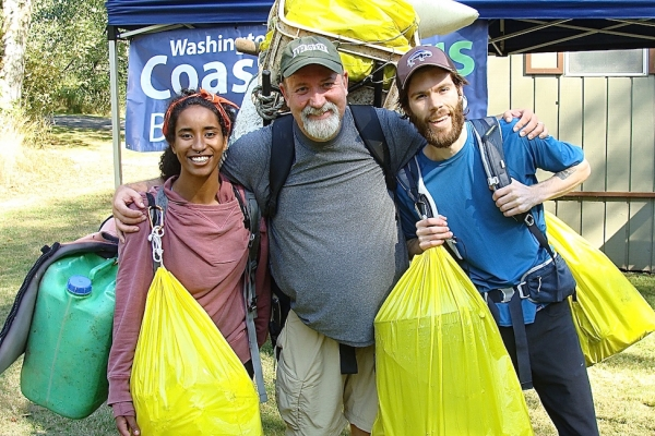 Three people holding bags of debris.