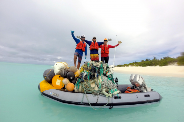 Members of the marine debris team stand proudly on top of a large pile of debris.